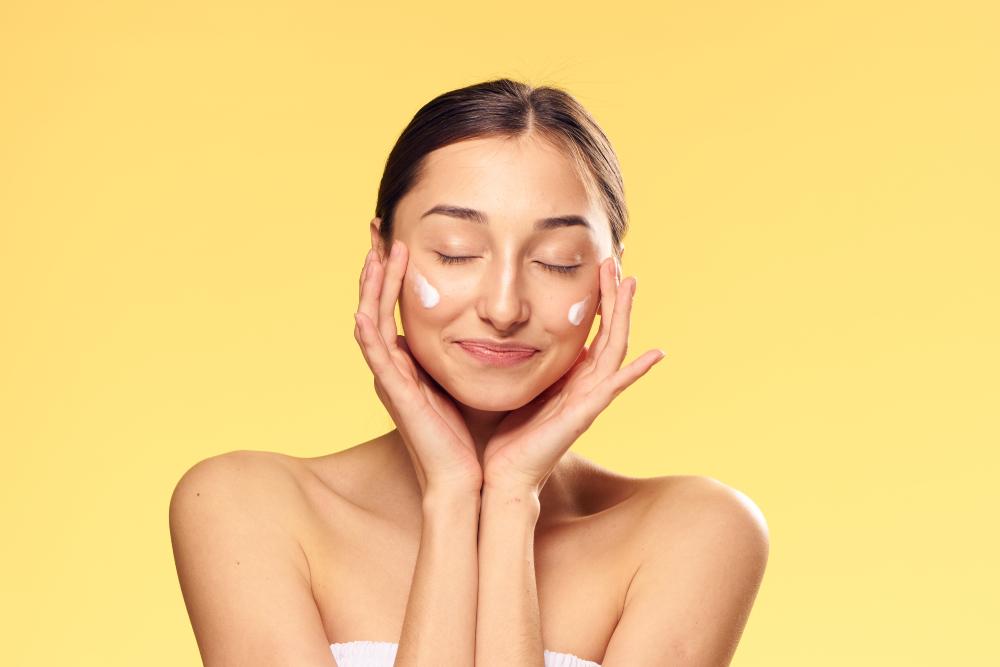 Mujer aplicándose crema hidratante en las mejillas
